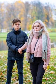 Twee verliefde tieners in ruzie. het blonde meisje neemt aanstoot aan jongen, kerel houdt haar hand vast,