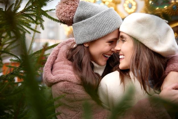 Twee verliefde vrouwen naast een kerstboom
