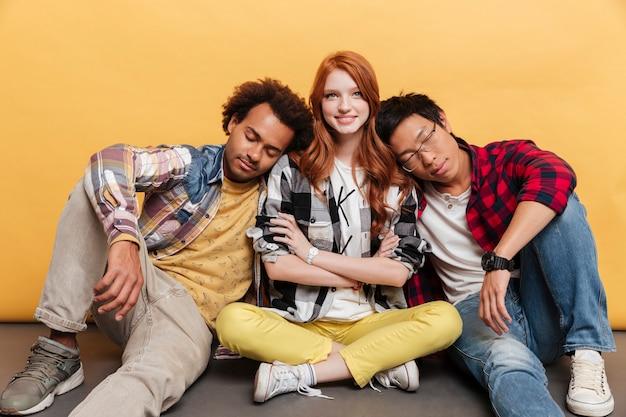 Twee vermoeide jonge mannen zitten en slapen op de schouders van lachend meisje over gele achtergrond