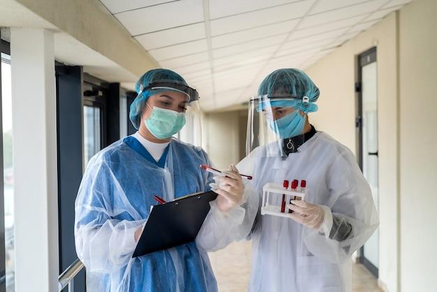 Twee verpleegkundigen werken met bloedmonsters om de uitkomst van een coronavirusinfectie te bepalen. teamwerk