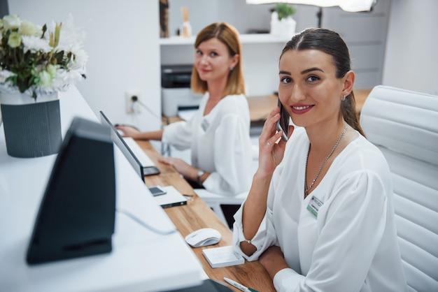Twee verpleegsters in wit uniform zitten bij de receptie van het ziekenhuis en doen hun werk.