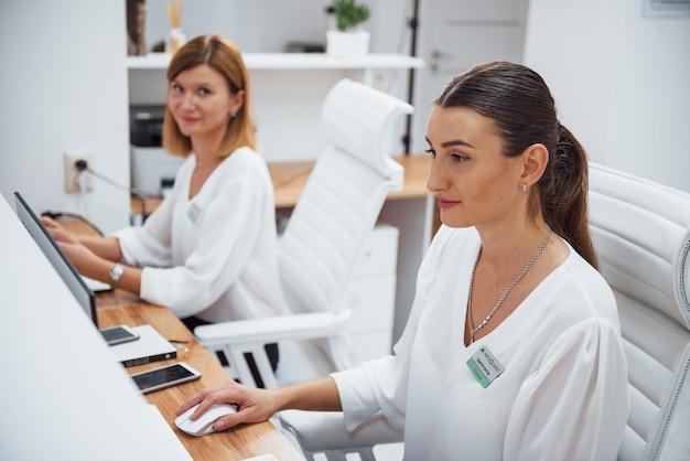 Twee verpleegsters in wit uniform zitten bij de receptie van het ziekenhuis en doen hun werk. Premium Foto
