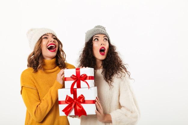 Twee verraste gelukkige meisjes in sweaters en hoeden die zich verenigen terwijl het houden van giften en omhoog het kijken over witte muur