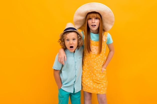 Twee verraste roodharige broer en zus kijken in zomerhoeden, op een geel