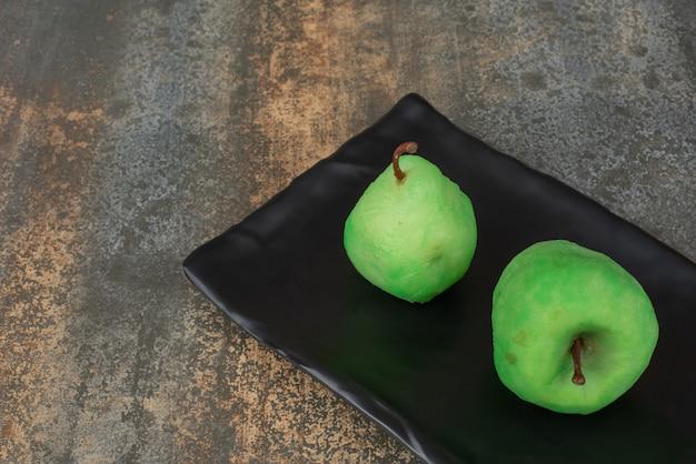 Twee vers geschilde appel op donkere plaat op marmeren oppervlak.