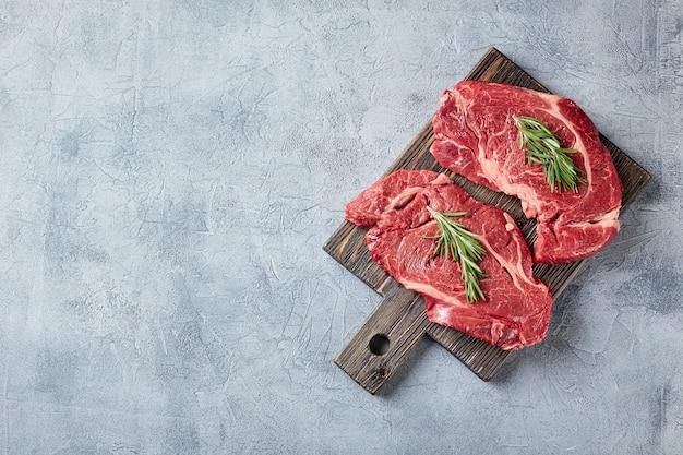 Twee vers rauw vlees prime black angus beef steak, rib eye, denver, op houten snijplank. bovenaanzicht, plaats voor tekst.