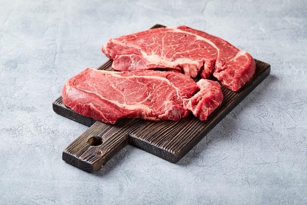 Twee vers rauw vlees prime black angus beef steak, rib eye, denver, op houten snijplank.