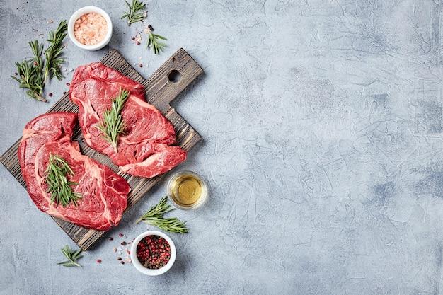 Twee vers rauw vlees prime black angus beef steaks, rib eye, denver, op houten snijplank. bovenaanzicht, plaats voor tekst.