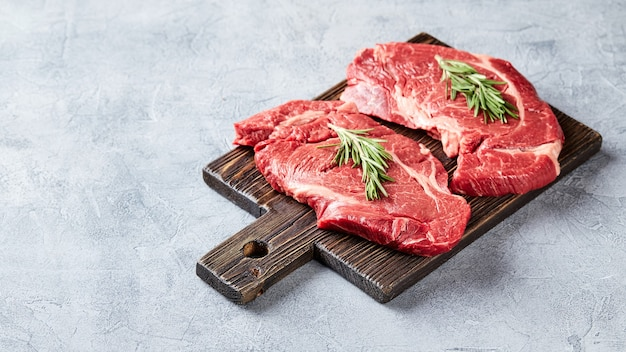 Twee vers rauw vlees prime black angus beef steaks, rib eye, denver, op houten snijplank. tplace voor tekst.