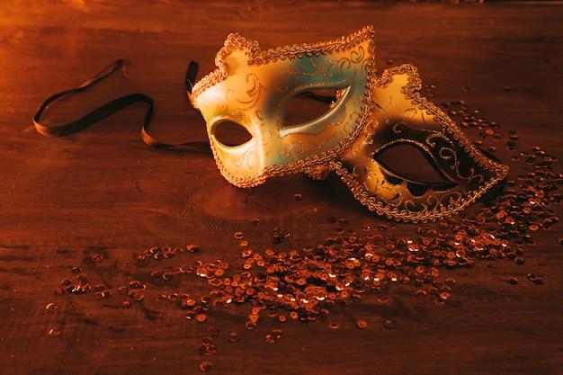 Twee verschillend type elegant venetiaans masker met lovertjes op donkere achtergrond