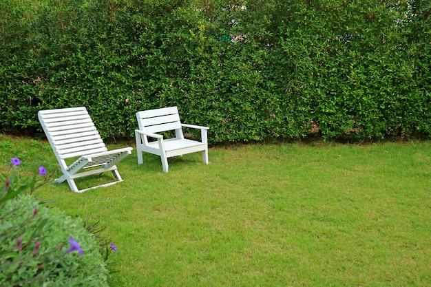 Twee verschillend type witte houten stoelen in levendige groene tuin