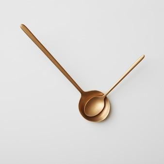 Twee verschillende gouden lepels gepresenteerd op een grijze achtergrond. tijd om te eten, lepels in de vorm van pijlen op het horloge, plat gelegd