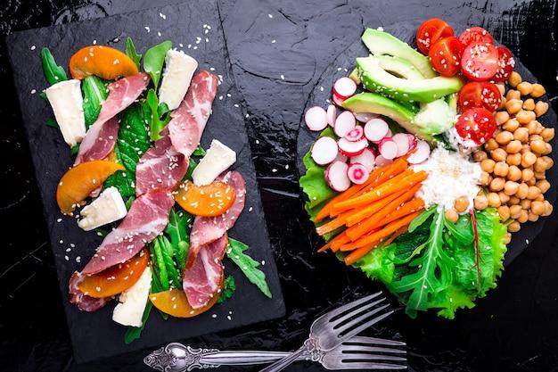 Twee verschillende salades op zwarte stenen leien