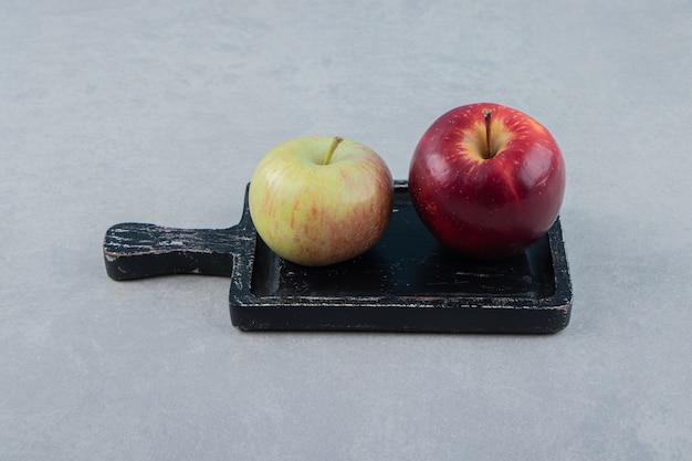 Twee verse appels op zwarte snijplank