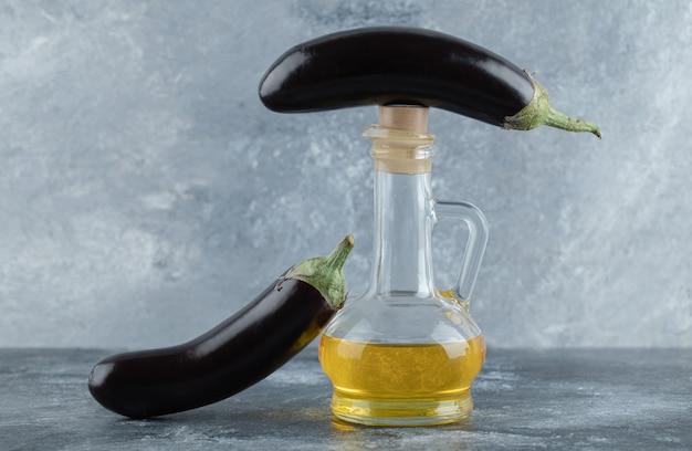 Twee verse aubergine met een fles olie op een grijze achtergrond.