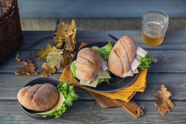 Twee verse broodjes ciabatta stokbrood met ham, kaas, sla en een glaasje bier
