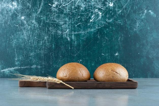 Twee verse broodjes op een houten bord met tarwe.