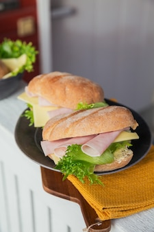 Twee verse ciabatta stokbrood sandwiches met ham, kaas en sla op rustieke houten achtergrond lettuce