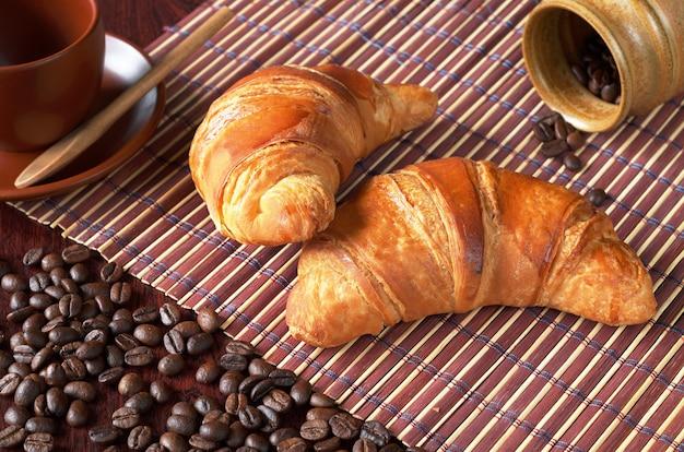 Twee verse croissants en koffiebonen op bamboe servet op tafel
