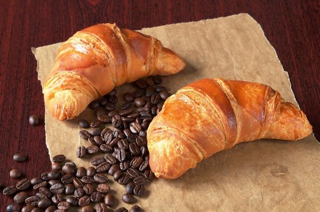 Twee verse croissants en koffiebonen op verfrommeld papier op de houten tafel