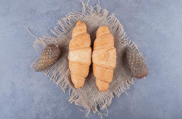 Twee verse croissants met decoratieve dennenappels over grijze achtergrond.