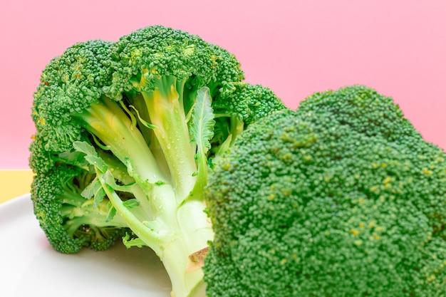 Twee verse en rauwe stukjes broccoli op witte plaat ongekookte groene kool