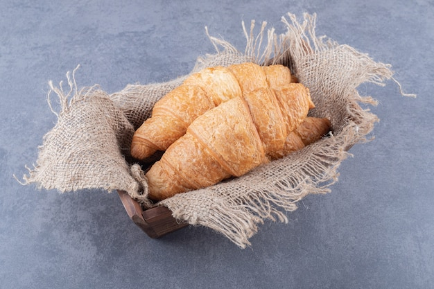 Twee verse franse croissant in houten kist.