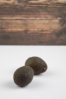 Twee verse gezonde bruine avocado geïsoleerd op wit-grijze achtergrond.