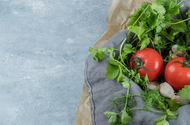 Twee verse hele tomaten op een grijs tafelkleed