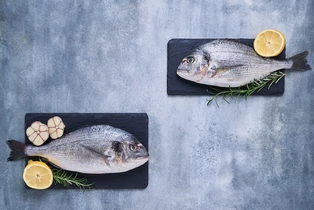 Twee verse koninklijke dorade op blauwe achtergrond gezond voedsel concept bovenaanzicht kopie ruimte