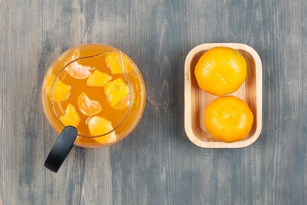 Twee verse mandarijnen met een glazen pot sap