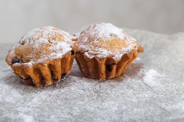 Twee verse muffins met bosbessen bestrooid met poedersuiker op een wazig papier verfrommeld