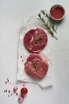 Twee verse parisienne rauwe biefstuk op wit perkamentpapier met zout, peper en rozemarijn in een rustieke stijl op oude houten achtergrond. zwarte angus. bovenaanzicht.