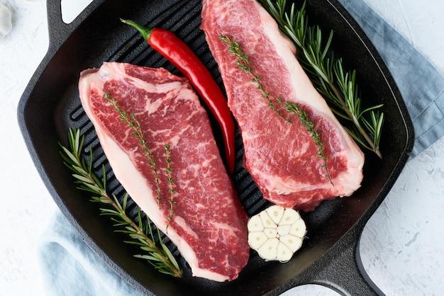 Twee verse rauwe grote stukken vlees, ossenhaas, marmerhaasje in grote gietijzeren pan.
