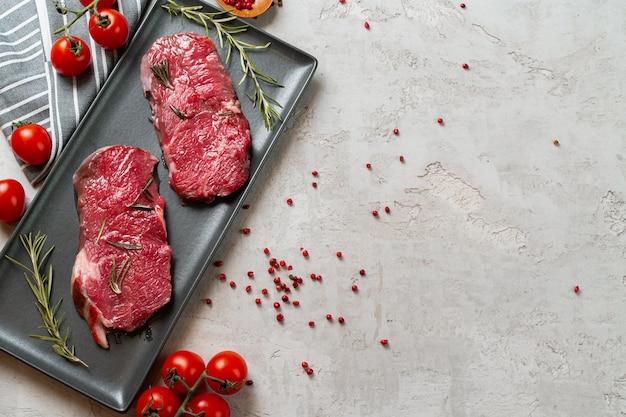 Twee verse rauwe vlees steaks op zwarte keramische plaat