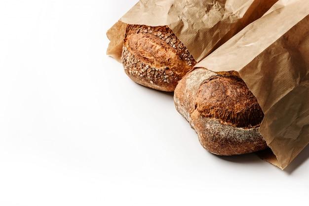Twee verse rustieke brood in ambachtelijke tassen