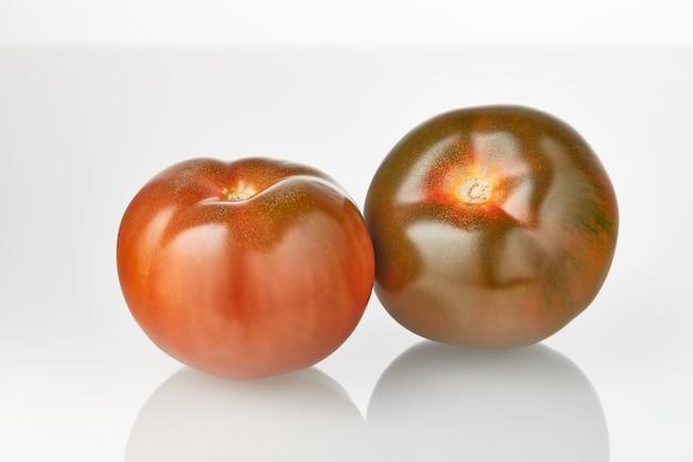 Twee verse sappige tomaten kumato vruchten geïsoleerd op de witte achtergrond.