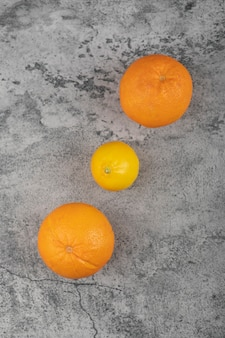 Twee verse sinaasappelvruchten met hele citroen op stenen tafel.