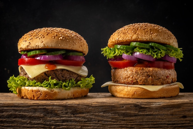 Twee verse smakelijke hamburgers op houten rustieke tafel.