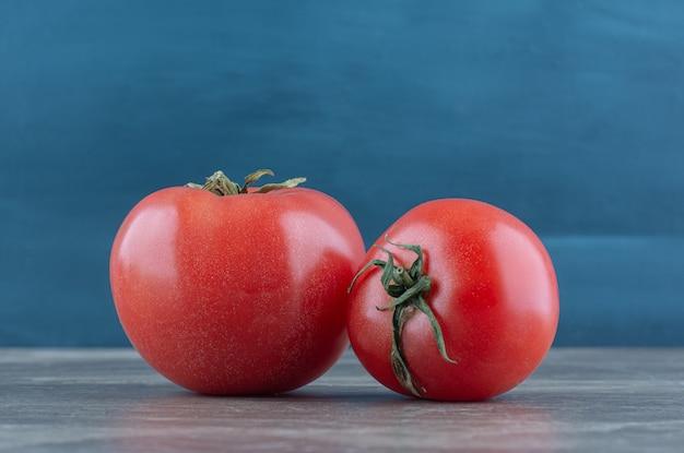 Twee verse tomaten, op de marmeren tafel.