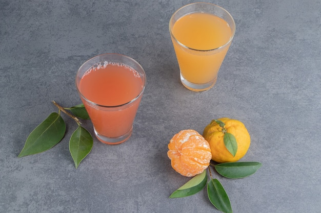 Twee verse vruchtensappen met bladeren en mandarijnen
