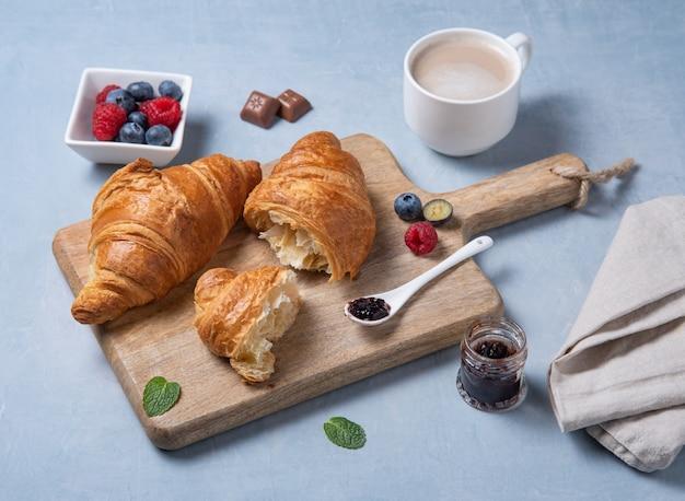 Twee verse warme glutenvrije croissants op een snijplank en een grijze servet met kopje koffie, jam, bosbessen en frambozen op een grijze achtergrond. plat lag