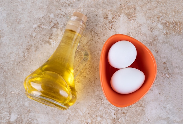 Twee verse witte kippeneieren met een glasfles olie