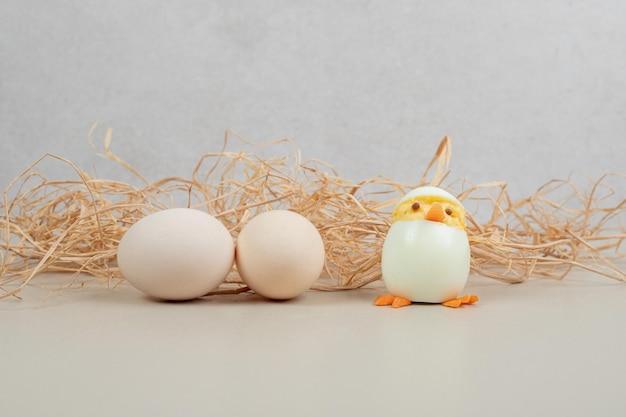 Twee verse witte kippeneieren met kippenstuk speelgoed en hooi.