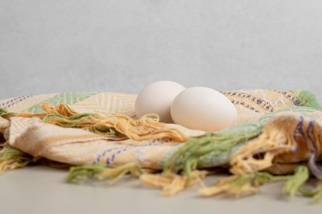 Twee verse witte kippeneieren op tafellaken.