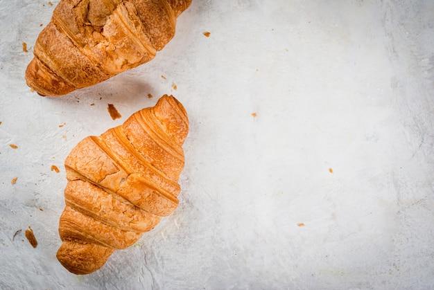 Twee verse zelfgemaakte croissants op een witte betonnen tafel. bovenaanzicht copyspace