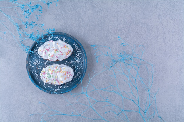 Twee verse zoete cupcakes met kleurrijke hagelslag en room op een blauwe houten bord.