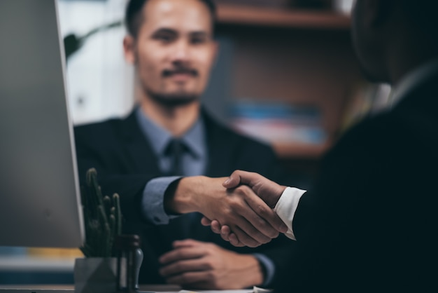 Twee vertrouwen zaken man handen schudden tijdens een bijeenkomst in het kantoor, succes, handel, begroeting en partner concept.