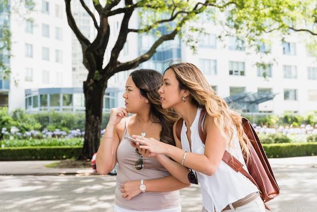 Twee verwarde jonge vrouwelijke toerist die zich in het park bevindt