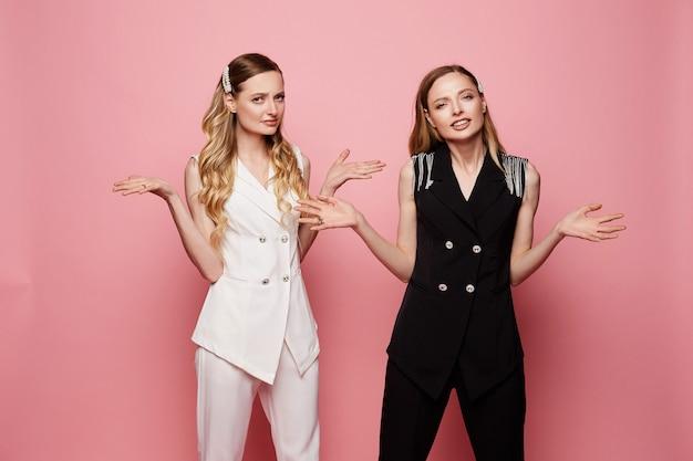 Twee verwarde vrouwelijke tweelingen in witte en zwarte trendy pakken